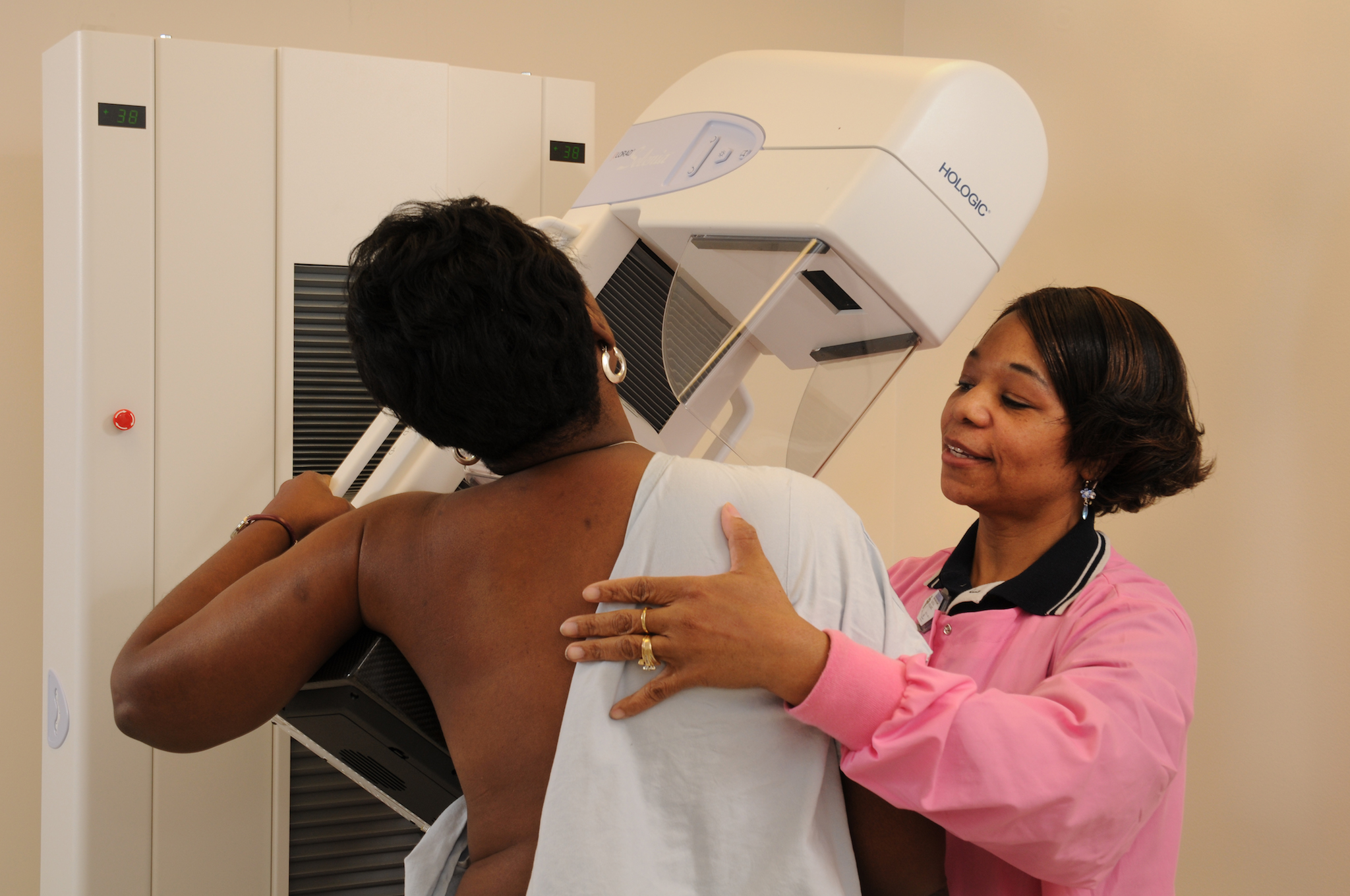 Image of mammorgraphy patient at mammogram machine with technician.